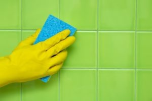 Cleaning bathroom green tile wall with sponge