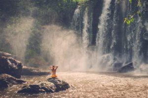 Woman outside in lake near waterfall