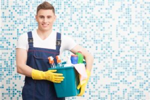 Man in overalls holding bucket of cleaning supplies