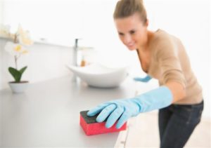 Woman cleaning bathroom countertop with sponge