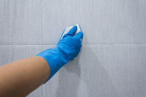 Person scrubbing bathroom tiles