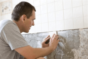 Man placing tiles on bathroom wall