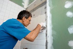 Man applying tiles to bathroom wall