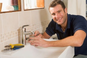 Man fixing sink faucet in bathroom