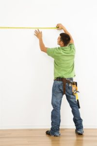 Man in green shirt measuring wall