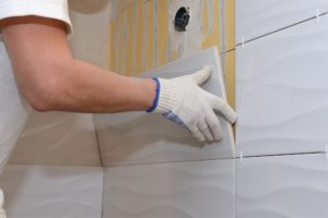 Man installing tiles on shower wall