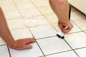 Man cleaning dirty tile floor with scrub brush