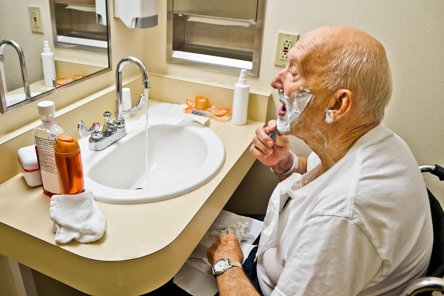 Elderly Man in Wheelchair Shaving at Bathroom Sink