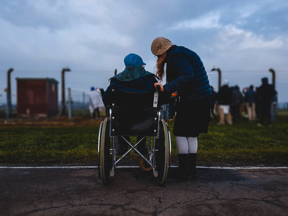 woman standing near person in wheelchair