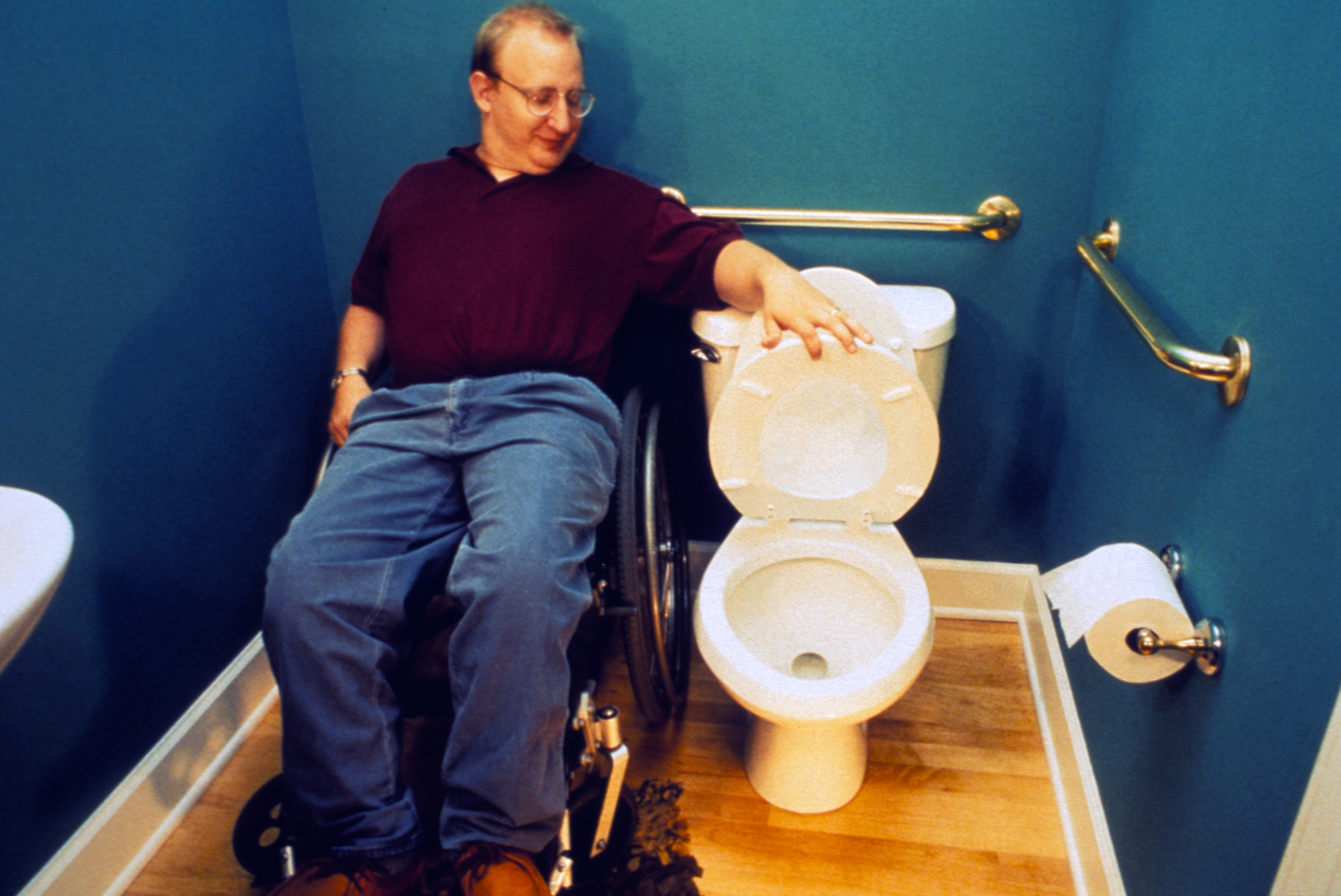 man sitting on wheelchair looking at the pot seat