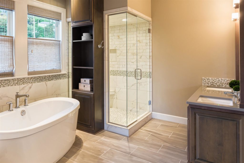 spacious tan and white master bathroom with dark wood vanity