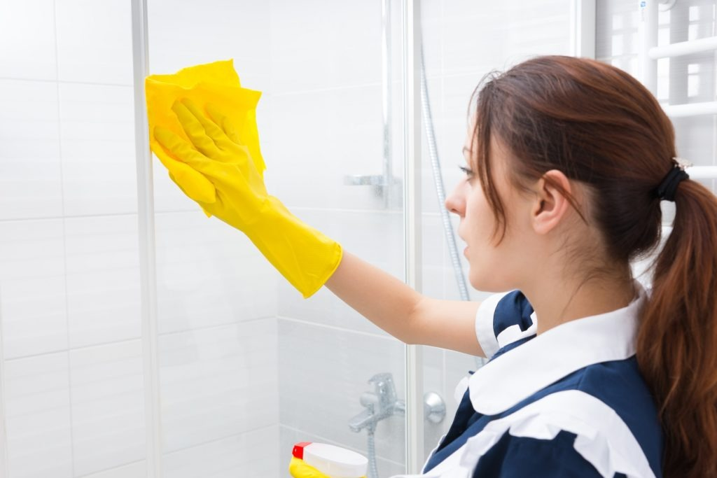 Housekeeper cleaning the glass shower cubicle
