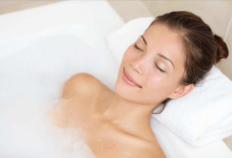 Bathing woman relaxing in bath smiling with eyes closed