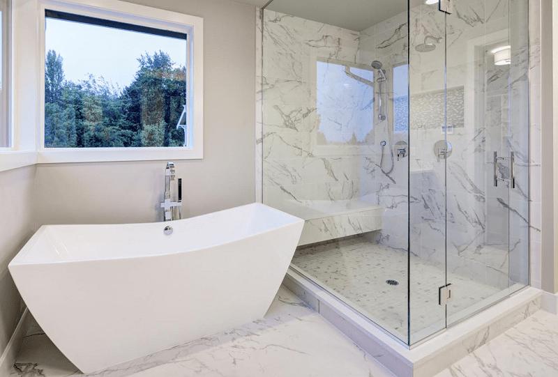 Sleek bathroom features freestanding bathtub front of glass shower