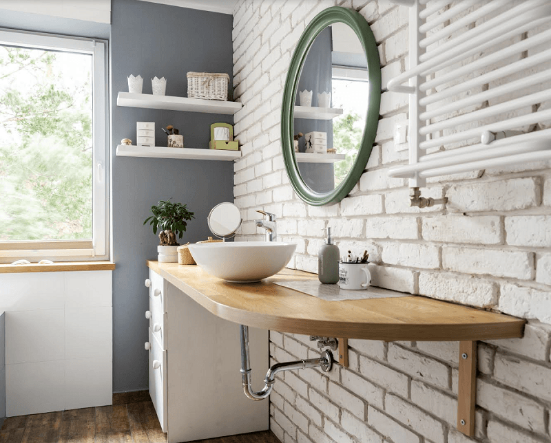 bathroom with wooden furniture and counter, round mirror and white brick wall