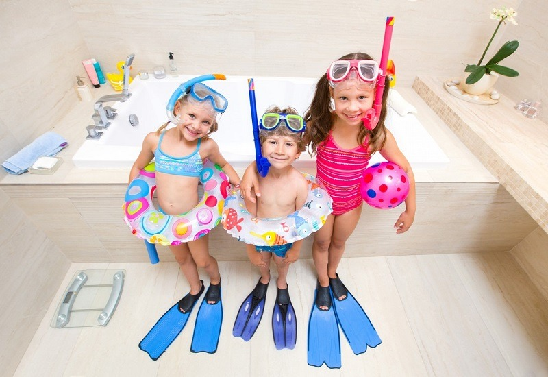 Little children in swimsuits play in the bathroom