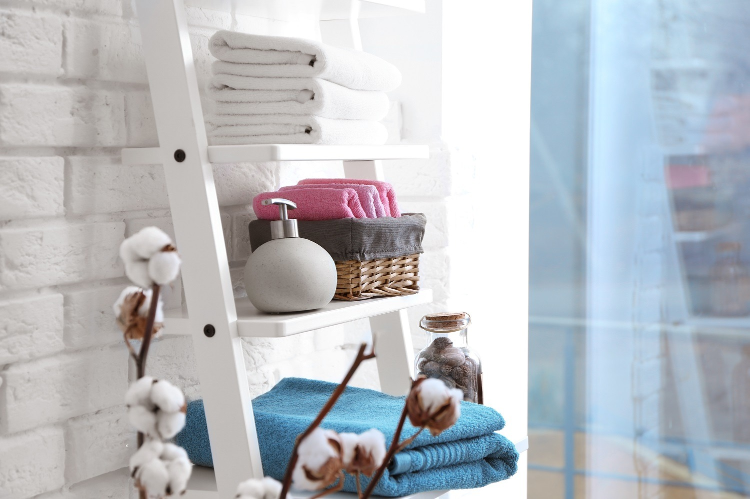 Clean towels with soap dispenser on shelves in bathroom