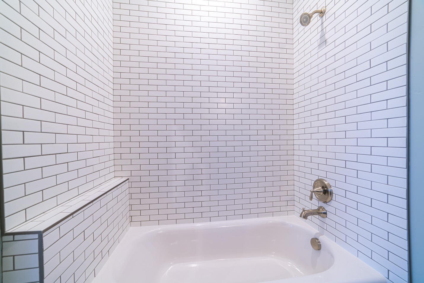 Clean white tiled shower combination tub bright interior