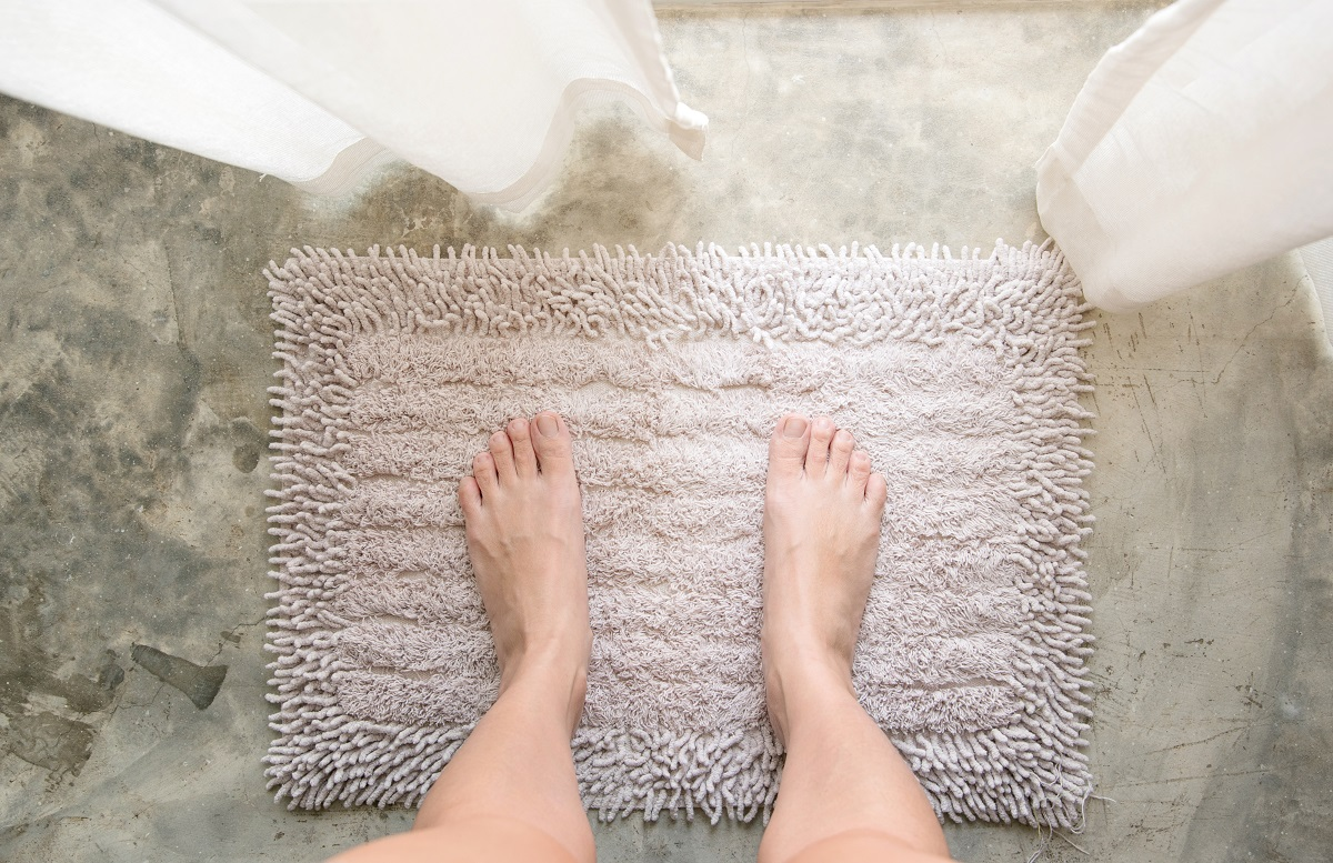 Woman feet standing on old white or grey carpet