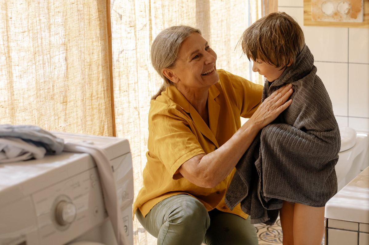 Granny wiping the boy with a towel.